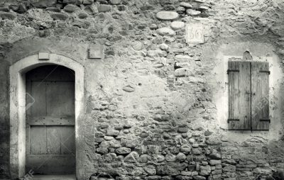 Old stone wall with door and window with closed shutters in black and white